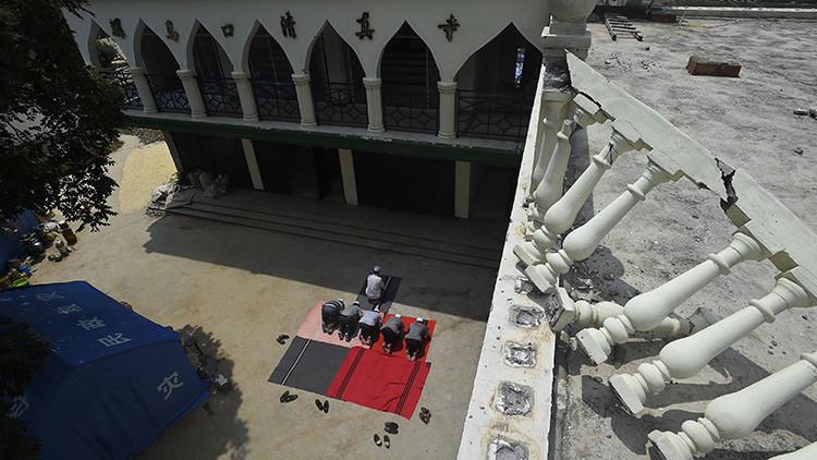 Unos musulmanes rezan en una mezquita dañada en la zona del terremoto en Longtoushan, condado de Ludian, Yunnan, China, 6 de agosto de 2014.